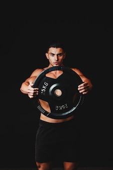 ダンベルを持ち上げる上半身裸の筋肉質の男
