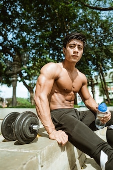 The shirtless muscular man sits holding a drinking bottle by the dumbbells after a hand muscle workout in the park