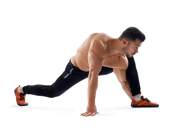 Shirtless muscular man stretching legs.