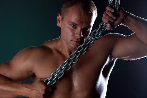 金属チェーンと上半身裸の筋肉男