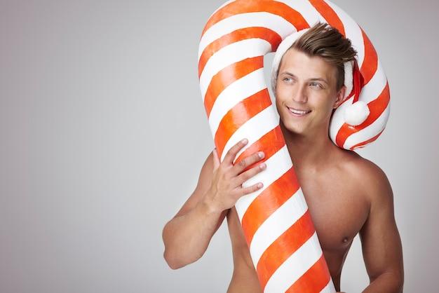 大きなキャンディケインと上半身裸のサンタ