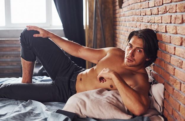 벗은 섹시한 남자는 아침 시간에 침실에서 혼자 휴식을 취합니다.