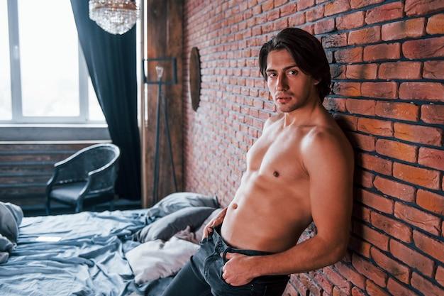 아침 시간에 침실에서 벽돌 벽에 기대어 벗은 섹시한 남자.