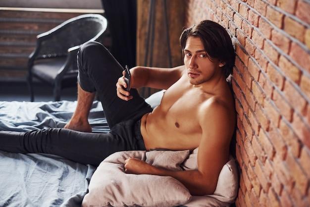 전화를 손에 들고 벗은 섹시한 남자는 아침 시간에 침실에서 혼자 휴식을 취합니다.