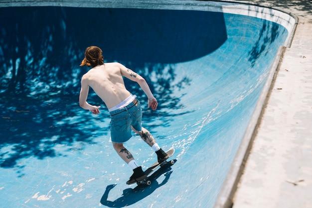 벗은 스케이트 보더 타기