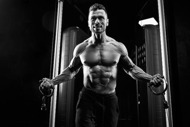 Shirtless sportsman doing crossover chest exercise.