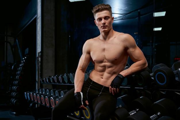 Shirtless sportsman posing in gym.