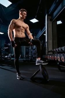 Без рубашки спортсмен позирует в тренажерном зале.