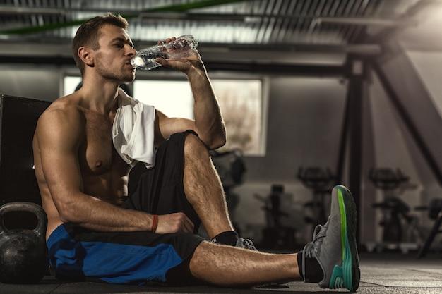 床の飲料水に座っているジムでトレーニングした後休んで上半身裸のスポーツマン