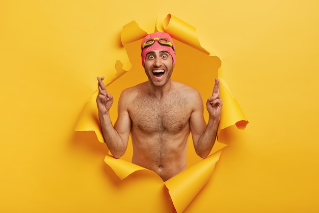 Shirtless 스포티 한 수영 선수는 고글과 함께 수영 모자를 착용하고 손가락을 교차시킵니다.
