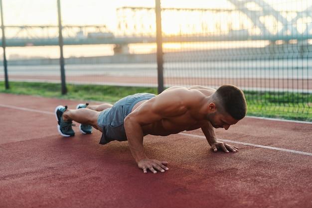 Сильный, преданный своему делу мускулистый мужчина без рубашки делает отжимания на корте по утрам.