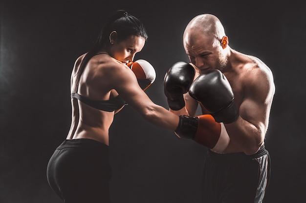 ボクシングと自己防衛のレッスンでトレーナーと運動している上半身裸の女性