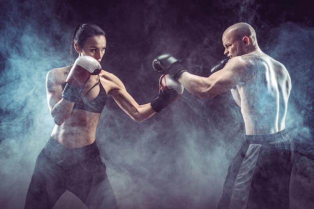 권투와 자기 방어 수업에서 트레이너와 함께 운동 벗은 여자 여성과 남성의 싸움