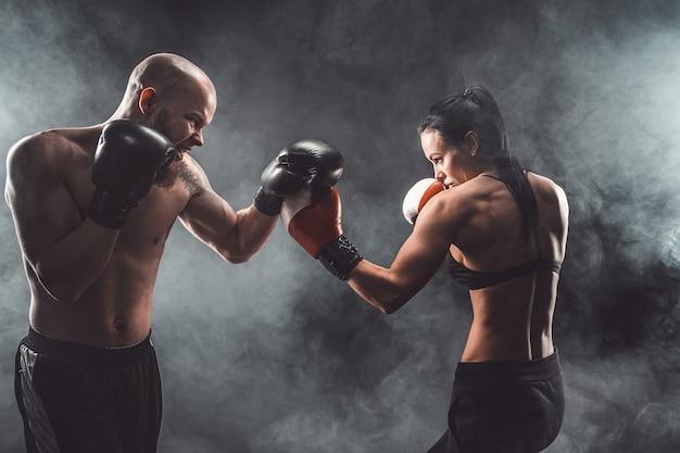 ボクシングと護身術のレッスン、スタジオ、暗い空間でトレーナーと運動する上半身裸の女性