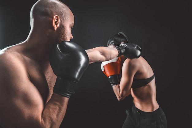 Женщина без рубашки, тренирующаяся с тренером на уроке бокса и самообороны, студии, дым в космосе
