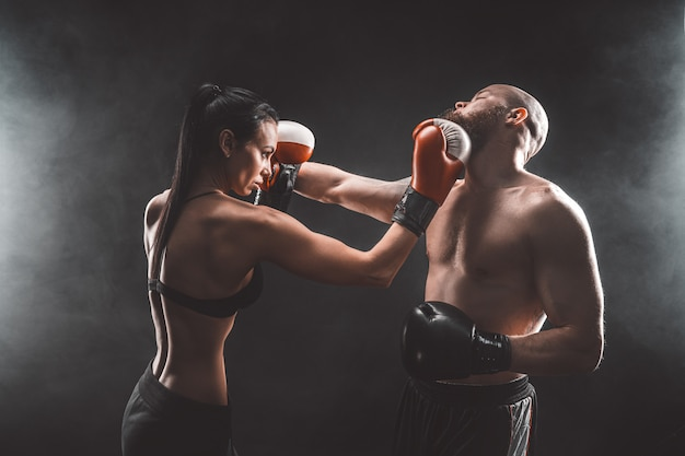 Shirtless woman exercising with trainer at boxing and self defense lesson, studio, dark background. female and male fight.