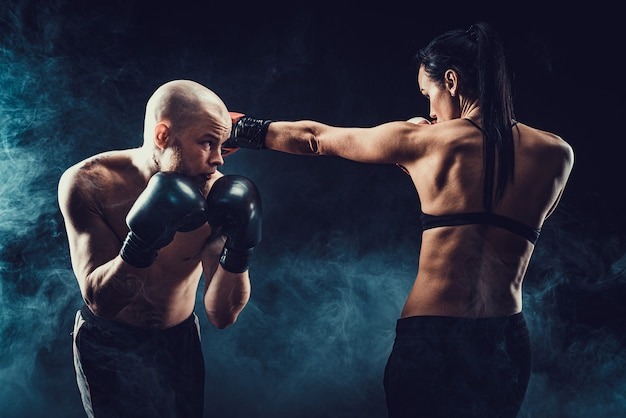 Shirtless woman exercising with trainer at boxing and self defense lesson, studio, dark space