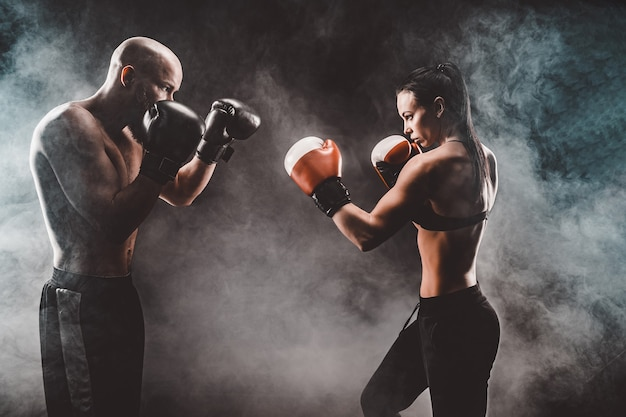 Shirtless woman exercising with trainer at boxing and self defense lesson, studio, smoke on space