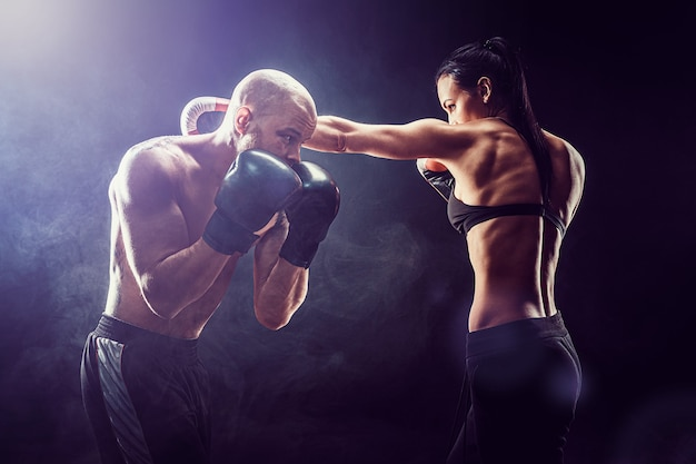 Shirtless woman exercising with trainer at boxing