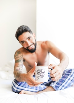 Shirtless young man holding cup of coffee