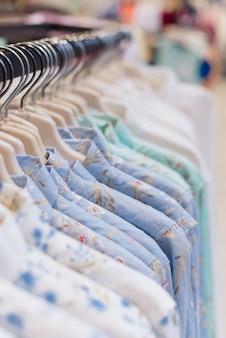 Рубашки вешают на вешалке в магазине