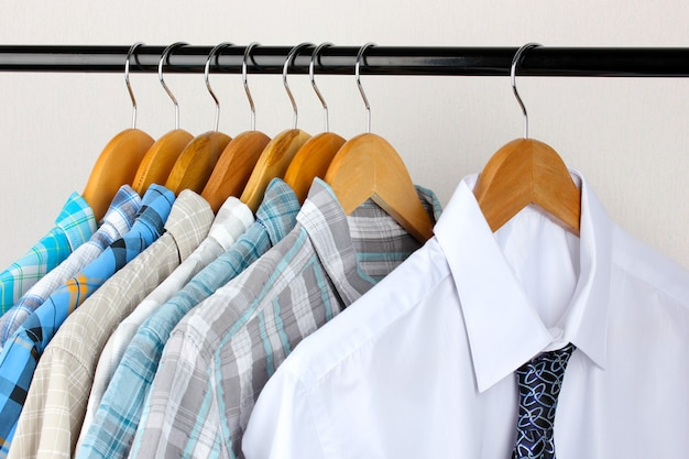 Shirts with ties on wooden hangers on white