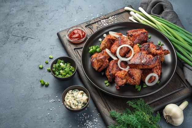 시시 케밥은 회색 배경에 양파와 신선한 허브가 있는 접시에 놓여 있습니다. 측면 보기, 수평.