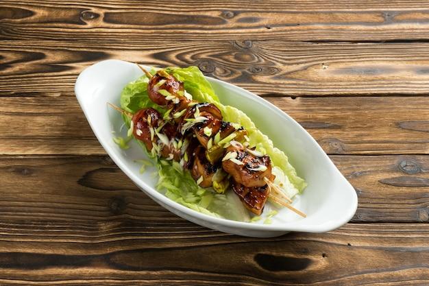 Шашлык из курицы и кабачков в соусе терияки с листьями салата и зеленым луком в красивой керамической тарелке на деревянном кухонном столе.