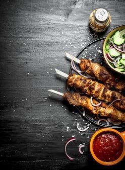 돼지 고기와 샐러드의 시시 케밥. 검은 나무 테이블에.