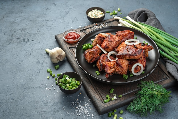 어두운 회색 배경에 양파와 허브와 함께 접시에 시시 케밥. 측면 보기, 복사를 위한 공간입니다.