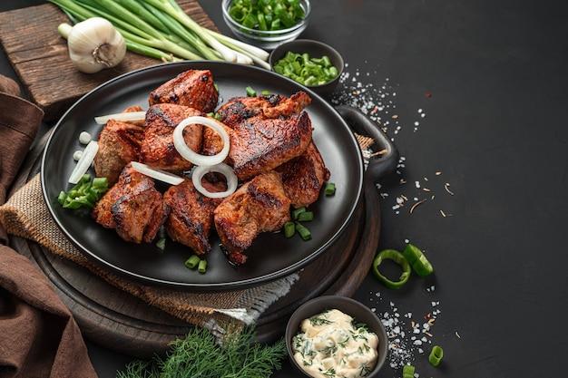 검은 배경에 양파와 함께 플래터에 시시 케밥. 고기 요리. 측면 보기, 클로즈업입니다.