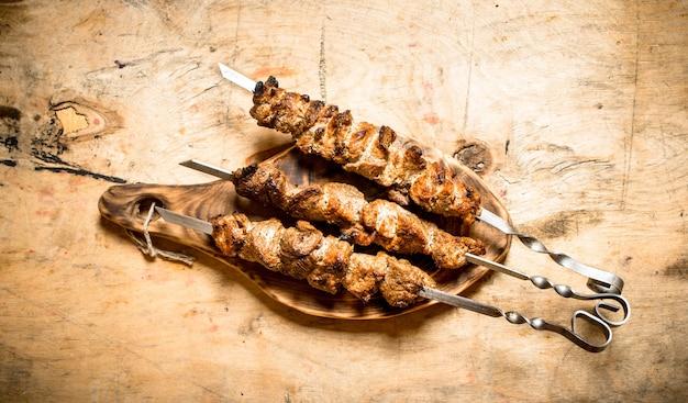 シシカバブの串焼き。木製のテーブルの上。