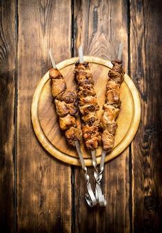 串焼きのシシカバブ。木製の背景に。