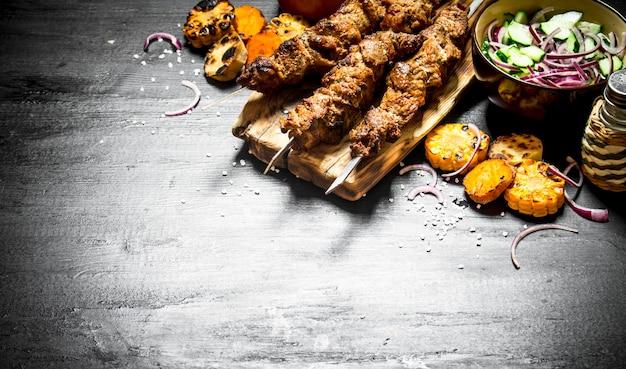 グリル野菜と新鮮なサラダを添えた串焼きのシシカバブ。黒い木製のテーブルの上。