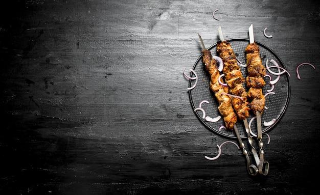 양파와 꼬치에 시시 케밥. 검은 나무 테이블에.