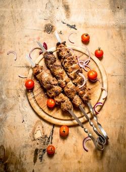 トマトの串焼きにシシカバブ。木製のテーブルの上。