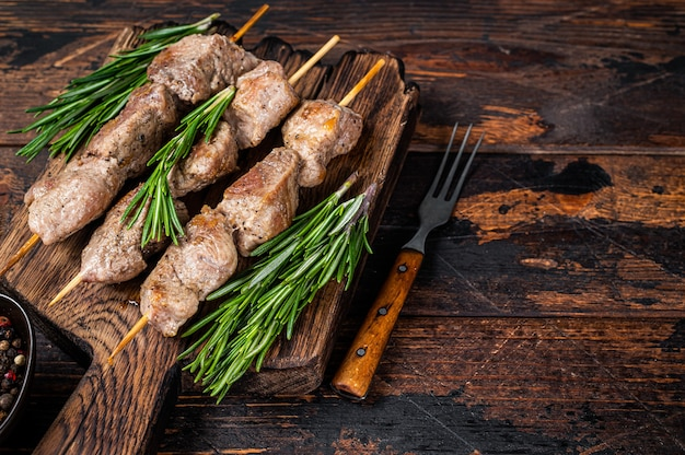 Shish kebab on skewers with herbs  on a wooden board. dark wooden background. top view. copy space.