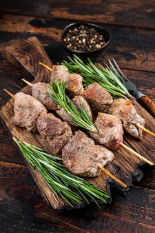 Shish kebab on skewers with herbs  on a wooden board. dark wooden background. top view.