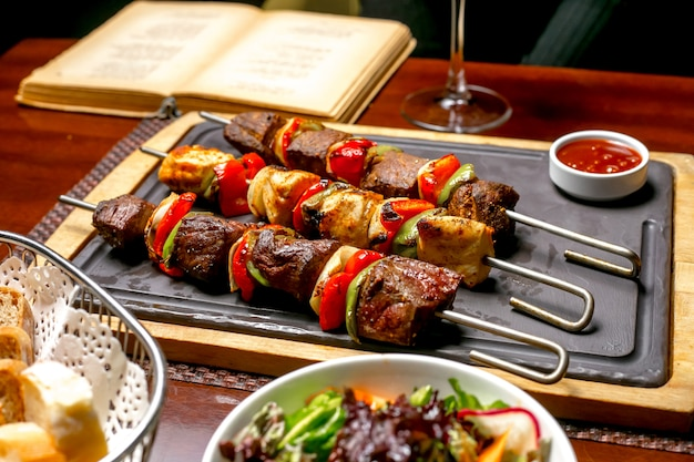 Shish kebab with colorful bell peppers served with ketchup and fresh vegetables