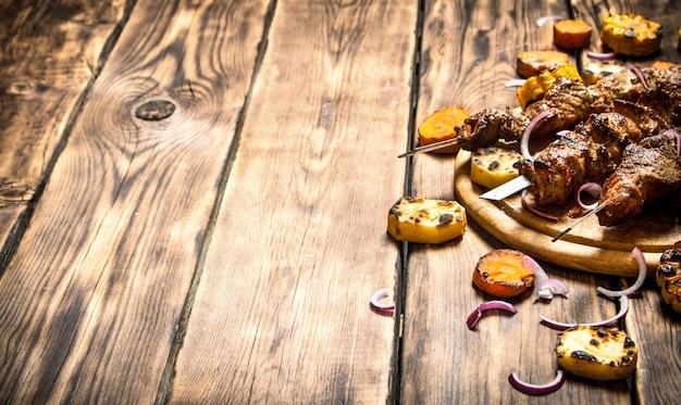 シシカバブと野菜のグリル。木製の背景に。