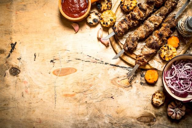 シシカバブのサラダ、野菜、ビール。木製のテーブルの上。