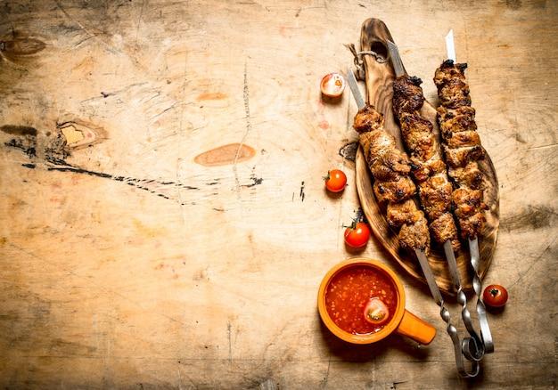 シシカバブとトマトソース。木製のテーブルの上。