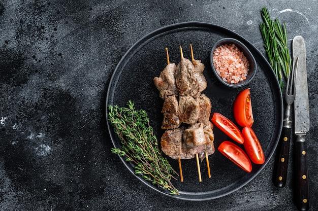 シシカバブは肉や野菜を皿に焼きました。黒いテーブル。上面図。スペースをコピーします。