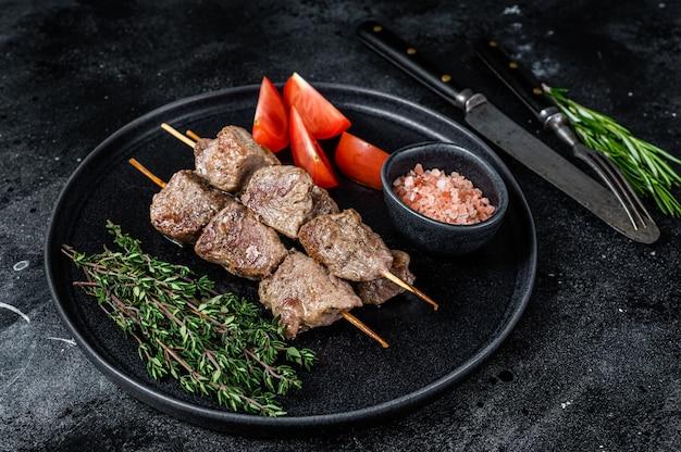 シシカバブは肉や野菜を皿に焼きました。黒いテーブル。上面図。