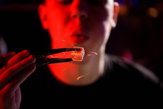 Shisha hookah, red hot coals. man blows coals for sparks fly.