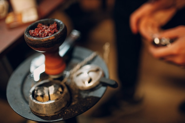 Shisha hookah tobacco putting in bowl for smoking and leisure