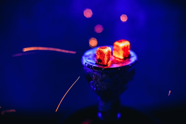 Shisha hookah with glowing red embers and flying sparks in the bowl on blue background