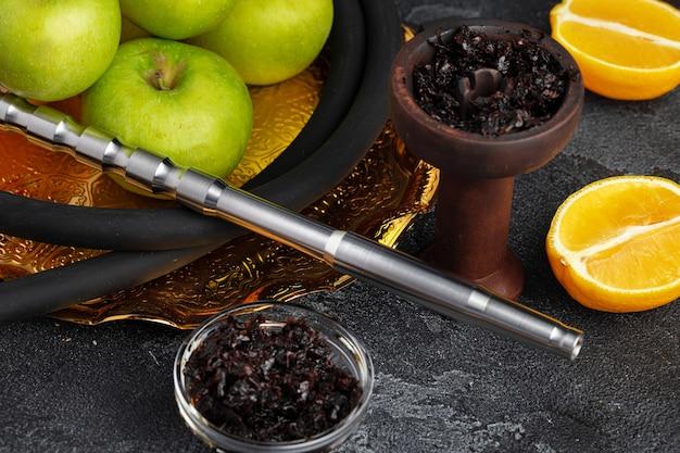 Shisha parts with apples and lemons on table