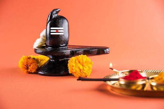 Shiva linga decorated with flowers & bel patra or leaf and haldi kumkum for pooja or worshipping of lord shiva or shankar bhagwan
