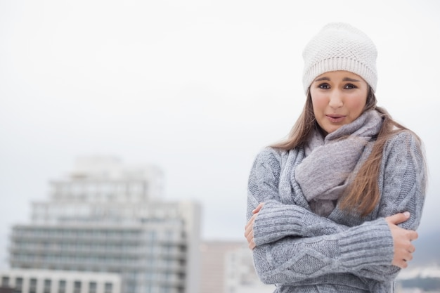 Shivering cute brunette with winter clothes on posing